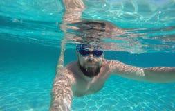 Man doing underwater selfie shot in deep blue sea Royalty Free Stock Photography