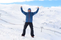 Man doing victory sign after peak summit trekking achievement in snow mountain on winter landscape Royalty Free Stock Photo