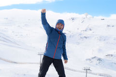 Man doing victory sign after peak summit trekking achievement in snow mountain on winter landscape. Young happy man doing victory sign after peak summit trekking Stock Photo