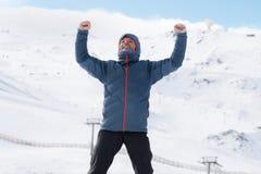Man doing victory sign after peak summit trekking achievement in snow mountain on winter landscape. Young happy man doing victory sign after peak summit trekking Royalty Free Stock Photos