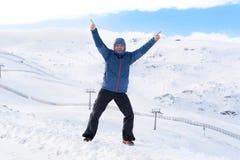 Man doing victory sign after peak summit trekking achievement in snow mountain on winter landscape. Young happy man doing victory sign after peak summit trekking Stock Photos