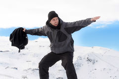 Man doing victory sign after peak summit trekking achievement in snow mountain on winter landscape. Young happy man doing victory sign after peak summit trekking Royalty Free Stock Photography