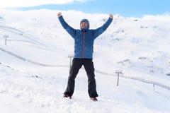 Man doing victory sign after peak summit trekking achievement in snow mountain on winter landscape. Young happy man doing victory sign after peak summit trekking Royalty Free Stock Image