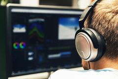 Man doing video editing on computer. With headphones on Stock Photo