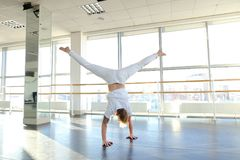 Man doing vigorous movements and swipe. Male person making swipe and vigorous movements in white shirt and pants. Blonde dancer training at studio with large Royalty Free Stock Images