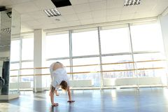 Man doing vigorous movements and swipe. Male person making swipe and vigorous movements in white shirt and pants. Blonde dancer training at studio with large Royalty Free Stock Photos