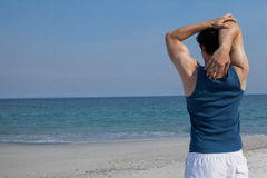 Man doing warm up on beach. Rear view of man doing warm up on beach Royalty Free Stock Photography