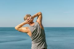 Man doing a warm-up exercise on the ocean. Fresh air and a healthy lifestyle stock image