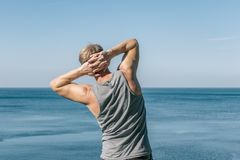 Man doing a warm-up exercise on the ocean. Fresh air and a healthy lifestyle stock photo