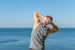 Man doing a warm-up exercise on the ocean. Fresh air and a healthy lifestyle royalty free stock photography