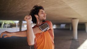 Portrait of a smiling athlete young man listening to music on earphones doing stretching exercises and warming up under
