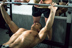 Man doing weight lifting with personal trainer Royalty Free Stock Image
