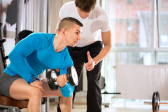 Man doing weights lifting with trainer Royalty Free Stock Image