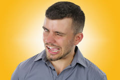 Man doing a wink. Young man doing a wink over a yellow background Royalty Free Stock Images