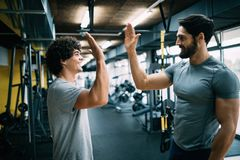 Man doing workout with a personal trainer. Young men doing workout with a personal trainer Stock Image