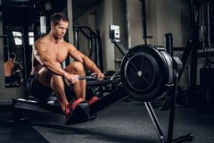 A man doing workouts on muscles of a back on power weight machin. Shirtless athletic male doing workouts on muscles of a back on power weight machine in a gym Royalty Free Stock Image