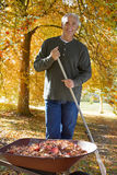 Man doing yard work in autumn Stock Photo