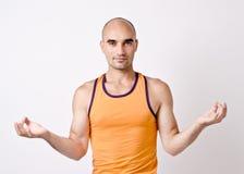 Man doing yoga. Bald man in orange tank top in yoga position, hands is aakash mudra Stock Photos