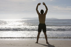 Man doing yoga on the beach Royalty Free Stock Photos