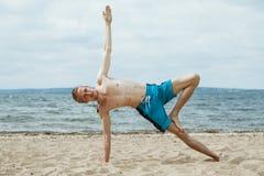 Man doing yoga on the beach Royalty Free Stock Image