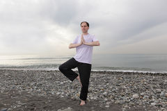 Man doing yoga on beach Stock Image