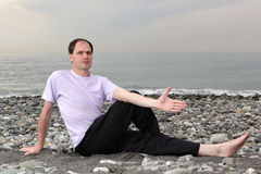 Man doing yoga on beach Stock Images