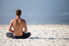 Man doing yoga on the beach Royalty Free Stock Image