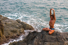 Man doing yoga exercise on the deserted wild stone sea beach. Royalty Free Stock Image