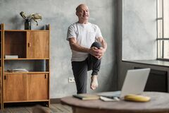 Man doing yoga exercise at home using online lesson on notebook