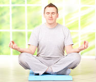 Man doing yoga exercise on mat Royalty Free Stock Images
