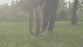 A man doing yoga exercises in the park. No grading version. Close up of a man doing yoga exercises in the park. Uttanasana stock footage