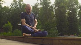 A man doing yoga exercises in the park. Padmasana stock video