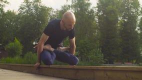 A man doing yoga exercises in the park. Padmasana, mayurasana stock video footage