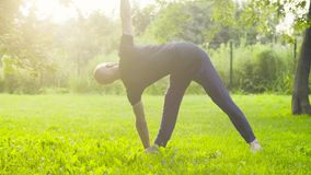 A man doing yoga exercises in the park. Utthita trikonasana stock video