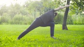 A man doing yoga exercises in the park. Utthita trikonasana stock video footage