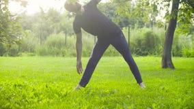 A man doing yoga exercises in the park. Utthita trikonasana stock footage