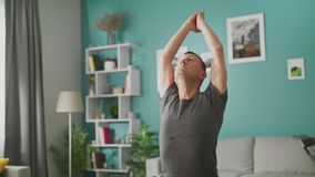 Man are doing yoga at home in the morning in his living room stock video