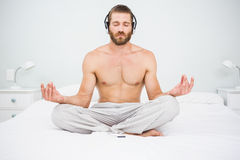 Man doing yoga while listening to music on bed Royalty Free Stock Images