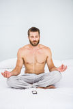 Man doing yoga while listening to music on bed Stock Photos