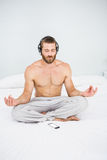 Man doing yoga while listening to music on bed Royalty Free Stock Photo
