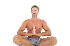 Man doing yoga and meditating on the floor Stock Photos
