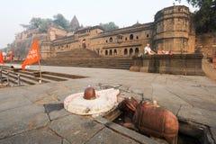 Man doing yoga and meditation in front of Maheshwar palace Stock Photo