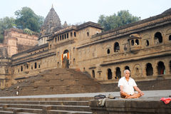 Man doing yoga and meditation in front of Maheshwar palace Stock Photos