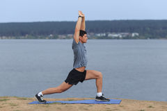 Man doing yoga outdoor. Young man practicing yoga fitness exercise outdoor at beautiful sea. Stock Image