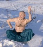 Man doing yoga over snow in winter. Men in green clothes practicing yoga over snow royalty free stock photos