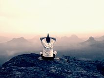 Man is doing Yoga pose on the rocks peak within misty morning Stock Photo