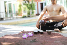 Man doing Yoga and pot of tea Royalty Free Stock Image