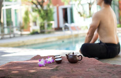 Man doing Yoga and pot of tea Royalty Free Stock Photos