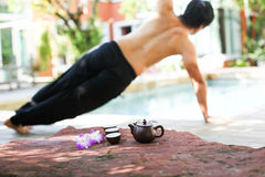Man doing Yoga and pot of tea Stock Image
