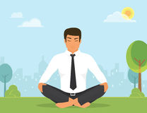 Man is doing yoga and sitting in the lotus position in the park Royalty Free Stock Photo